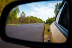 Rearview car driving mirror view forest road stock photos