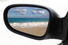 Rearview car mirror tropical caribbean beach. Rearview car driving mirror view tropical caribbean sea turquoise beach Royalty Free Stock Images