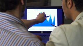 Rearview cercano para arriba de dos hombres de negocios que discuten el diagrama en la pantalla del ordenador portátil almacen de video