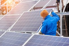 Professional electrician worker installing solar panels. Rearview horizontal shot of a male electrician working on a power plant with solar panels renewable Stock Images