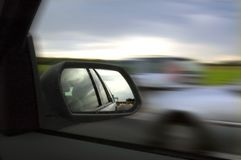 Rearview mirror. Rear view mirror with cars passing by, motion blur Royalty Free Stock Images