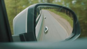 Rearview mirror of car moving along forest side asphalt road stock footage