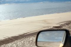 Rearview mirror of car on sandy sea beach with off road track stock photos