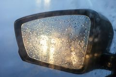 Rearview mirror with drops of water from the rain and a car with headlights. Selective focus, shallow DOF royalty free stock photography