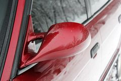 Rearview mirror. Part of a red car in the winter.  stock photography