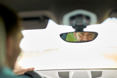Rearview mirror reflection of man driving car Royalty Free Stock Photos