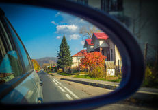 Rearview mirror with reflection. Rearview mirror. Road and house in reflection Stock Image