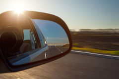 Rearview mirror and the setting sun from car Royalty Free Stock Photos