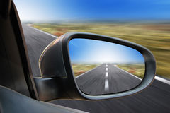 Rearview Mirror Traveling. A closeup of a rearview mirror on a car driving fast on a road. There is a zoom effect Royalty Free Stock Photo
