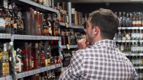 Rearview schot van een mens die wijn op de planken onderzoeken bij de supermarkt stock video