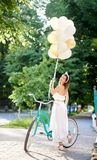 Happy woman holding baloons while riding bicycle. Rearview shot of a happy young beautiful woman smiling to the camera over her shoulder posing with a bicycle in Stock Photos