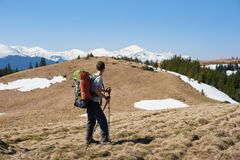 Male hiker with backpack in the mountains. Rearview shot of a man hiker with a backpack walking in the mountains copyspace sportsman athlete active lifestyle Royalty Free Stock Photography