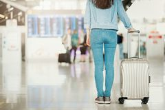 Woman standing in an airport with luggage Stock Photography