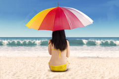 Rearview of woman under umbrella Stock Photos