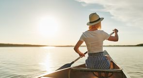 Young woman canoeing on a still lake in the summer royalty free stock photography