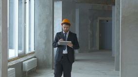 Reasltor, construction engineer, businessman inside a new building inspecting construction site using tablet. Construction engineer, businessman inside a new stock footage