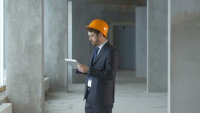 Reasltor, construction engineer, businessman inside a new building inspecting construction site using tablet. Construction engineer, businessman inside a new stock video