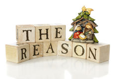 The Reason for the Season. Rustic alphabet blocks arranged to say, The Reason, with a small nativity scene (Mary, Joseph and Jesus only) to demonstrate that royalty free stock image