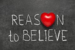 Reason to believe. Phrase handwritten on blackboard with heart symbol instead O stock photography
