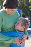 Reassurance. A mother parents her son at a playground royalty free stock image