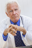 Reassuring Senior Male Doctor. A reassuring senior man male medical hospital doctor sitting at a desk wearing a shirt, tie and stethoscope Royalty Free Stock Images