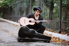 Reat and play. Young man reat and play acoustic guitar in the park stock photos