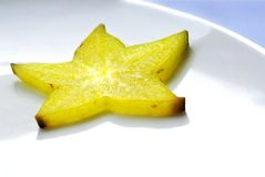 Rebanada amarilla del carambola en la placa blanca Fotos de archivo