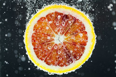 Rebanada anaranjada de la fruta cítrica que cae en el agua Foto de archivo