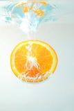 Rebanada anaranjada en agua Imágenes de archivo libres de regalías