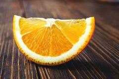 Rebanada anaranjada en una tabla de madera Fotografía de archivo libre de regalías