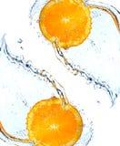 Rebanada anaranjada que cae y que salpica Imagen de archivo libre de regalías