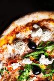 Rebanada caliente de la pizza con el salami, las aceitunas y el queso en un woode rústico Imagen de archivo libre de regalías