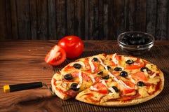 Rebanada caliente de la pizza con queso de fusión en una tabla de madera rústica Fotografía de archivo libre de regalías