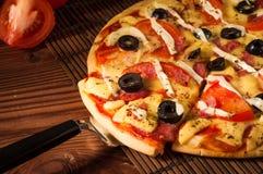 Rebanada caliente de la pizza con queso de fusión en una tabla de madera rústica Fotos de archivo