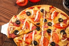 Rebanada caliente de la pizza con queso de fusión en una tabla de madera rústica Foto de archivo