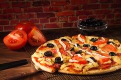 Rebanada caliente de la pizza con queso de fusión en una tabla de madera rústica Imagen de archivo libre de regalías