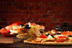 Rebanada caliente de la pizza con queso de fusión en una tabla de madera rústica Fotografía de archivo