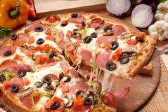 Rebanada caliente de la pizza con queso de fusi?n en una tabla de madera r?stica imagen de archivo libre de regalías