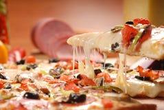 Rebanada caliente de la pizza con queso de fusi?n en una tabla de madera r?stica fotografía de archivo