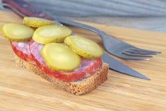 Rebanada conservada en vinagre del pepino de salchicha en un pedazo de pan Imagen de archivo
