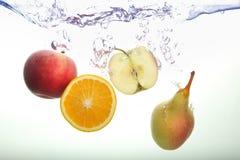 Rebanada de Apple, pera y chapoteo anaranjado en agua en el fondo blanco fotos de archivo libres de regalías