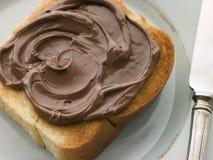 Rebanada de bollo de leche tostado con la extensión del chocolate Imágenes de archivo libres de regalías