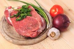 Rebanada de carne en la tabla de cortar con las especias, cebolla, ajo Foto de archivo
