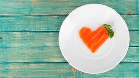 Rebanada de color salmón cruda en la forma del corazón en la placa blanca Fotografía de archivo libre de regalías