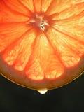 Rebanada de fruta anaranjada de la uva con un dropâ que se utilizará para el fondo fotografía de archivo libre de regalías