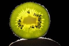 Rebanada de kiwi con el fondo negro Fotos de archivo libres de regalías