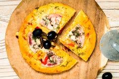 Rebanada de la pizza y cuchillo cercano de la pizza Fotografía de archivo libre de regalías