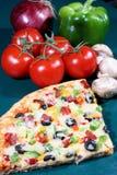 Rebanada de la pizza y verduras frescas Imagenes de archivo