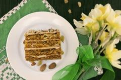 Rebanada de la torta con la nuez en la placa Ramo de narciso amarillo Foto de archivo