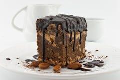 Rebanada de la torta de chocolate con la nuez en la placa en el fondo blanco Foto de archivo